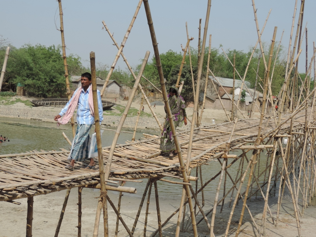 A padestrian uses the bamboo bridge.