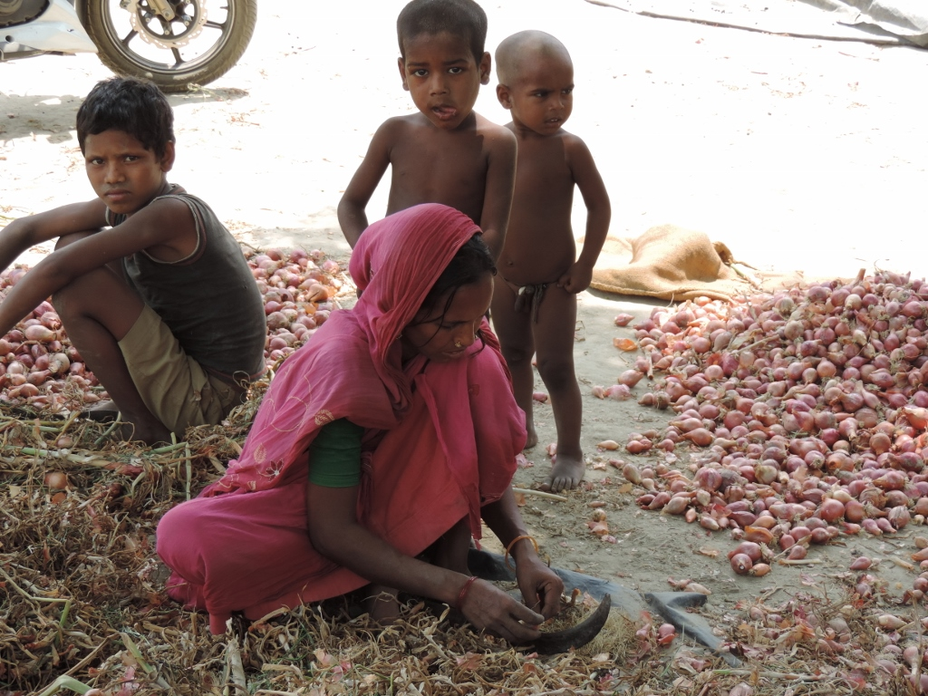 A woman at work in Banutola while her children look on