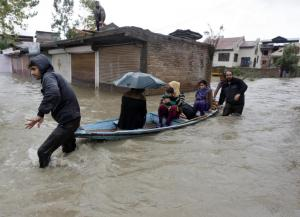 Kashmiri women and a child are transported in a boat through a flooded road in Srinagar | Photo : Reuters/Danish Ismail