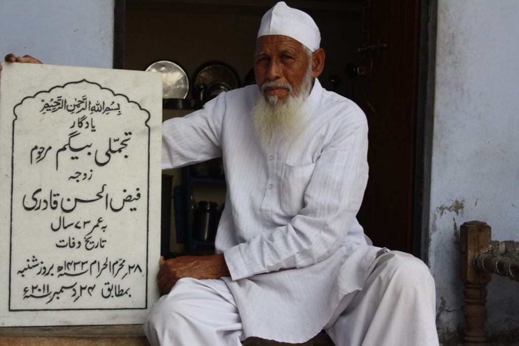 Qadri holding plaque for his wife's tomb