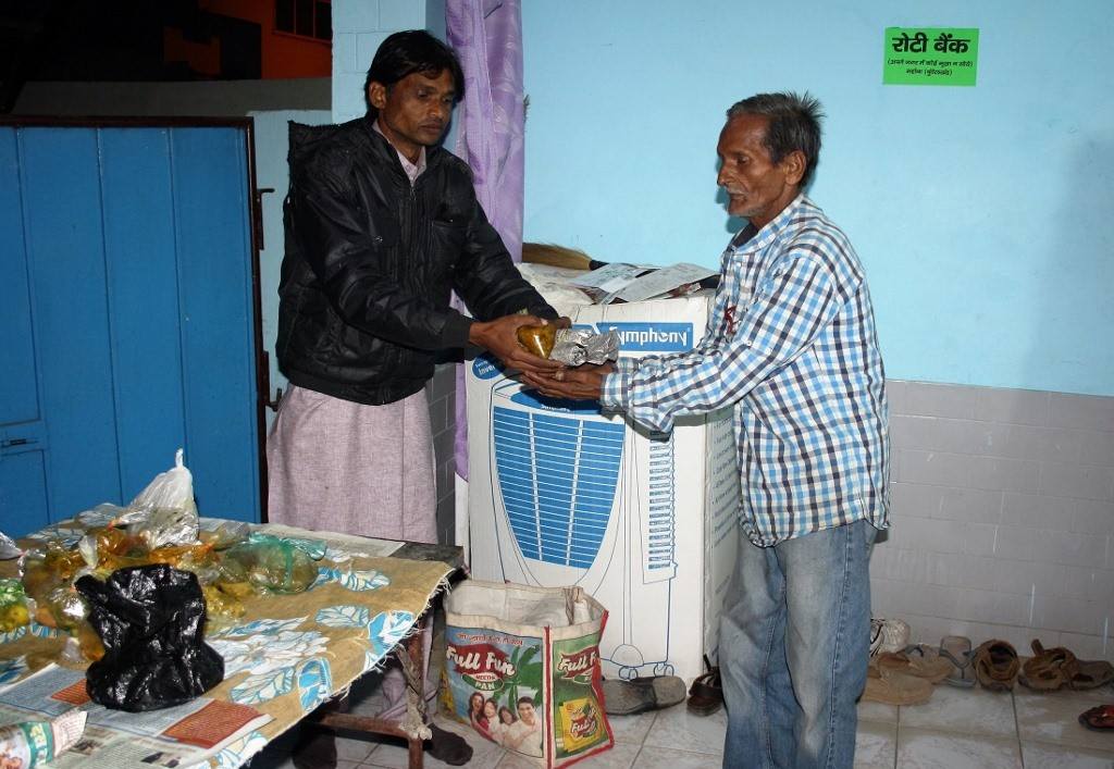 Father Labana giving food to Ashok Kumar Soni